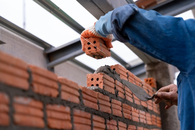 Feche a mão do pedreiro instalando a alvenaria de tijolo na parede externa do canteiro de obras