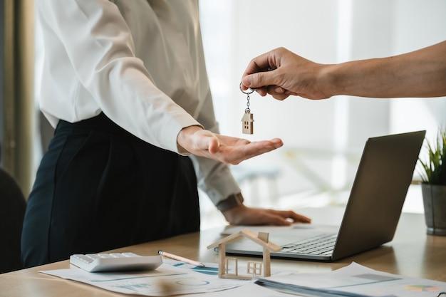 Feche a mão do proprietário do corretor de imóveis dando uma casa chave para o inquilino comprador no escritório moderno.