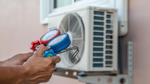 Feche a mão do técnico usando manômetro múltiplo para encher os condicionadores de ar.