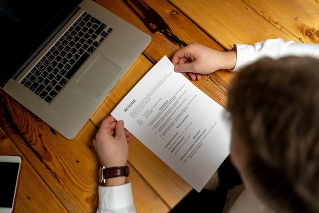 Feche a mão do trabalhador de escritório e leia o currículo na superfície de madeira