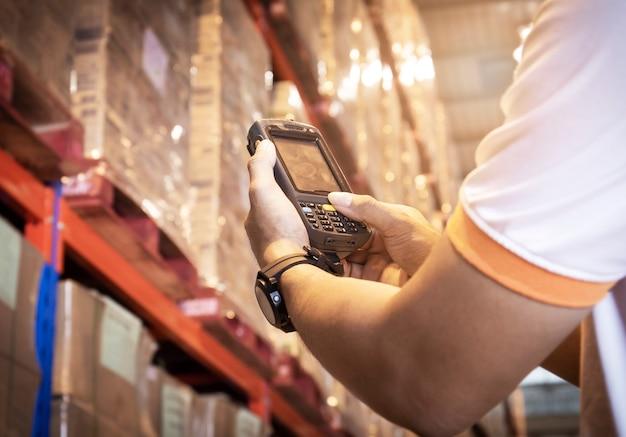 Feche a mão do trabalhador pressionando os botões do leitor de código de barras. equipamento informático para gestão de inventário em armazém.