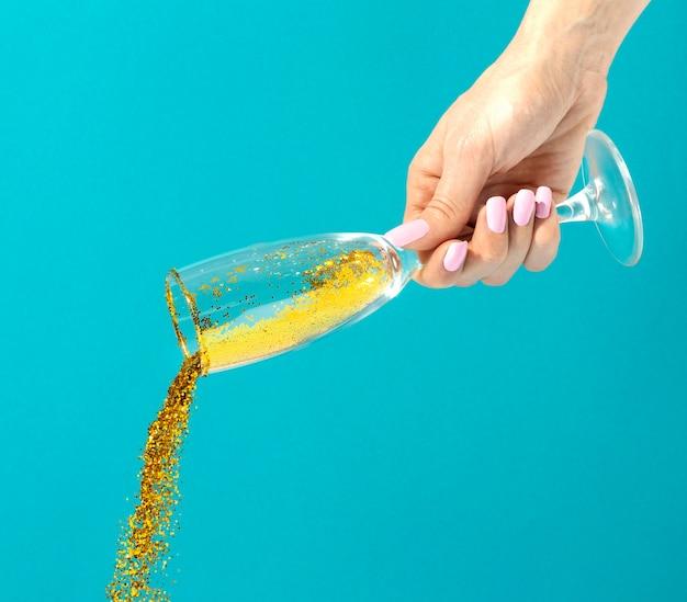 Feche a mão e o copo de glitter