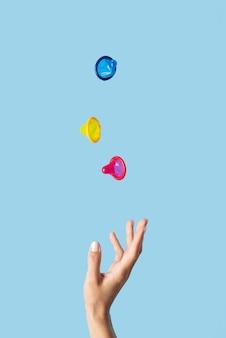 Feche a mão e preservativos coloridos