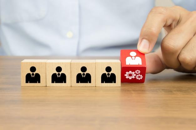 Feche a mão, escolhendo as pessoas com o ícone de roda dentada no brinquedo de madeira do cubo, conceitos de recursos humanos.