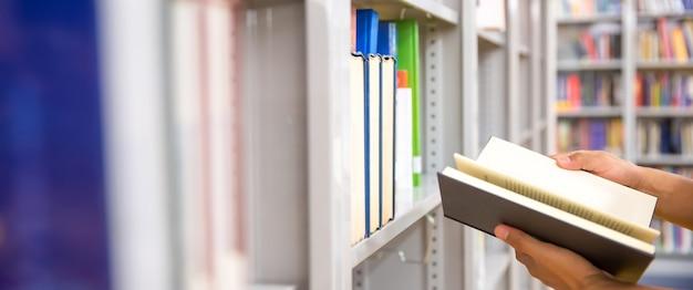 Feche a mão, escolhendo e abra um livro da estante.