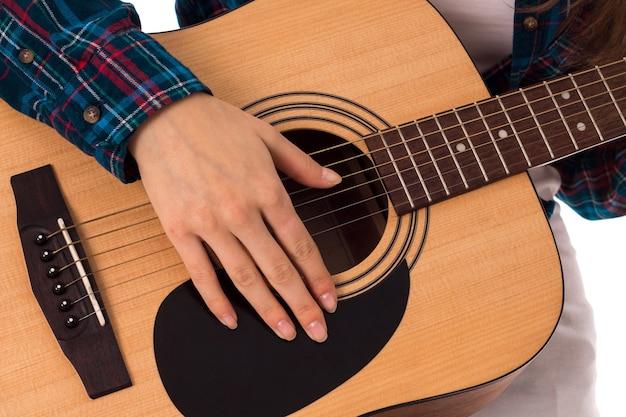 Feche a mão feminina com as cordas da guitarra no estúdio