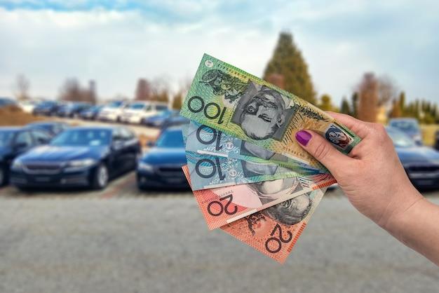 Feche a mão feminina com notas de dólar australiano