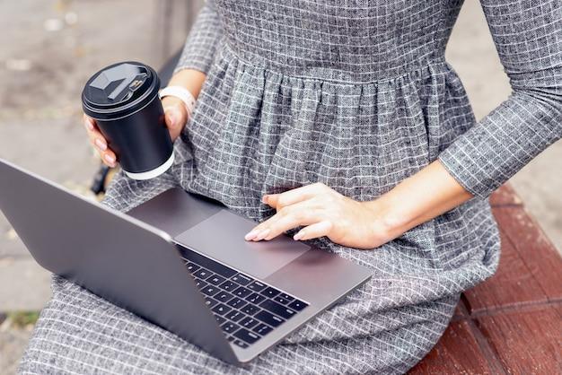 Feche a mão feminina está usando laptop enquanto segura uma xícara de café.