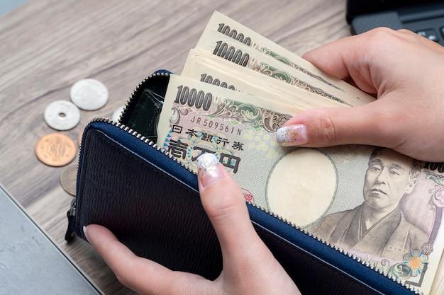 Feche a mão feminina segurando ienes japoneses 10000 notas