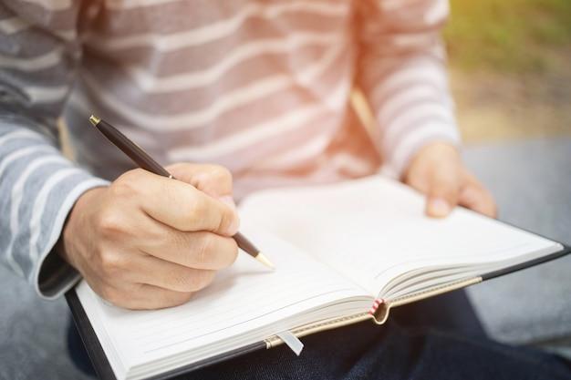 Feche a mão jovem está sentada em uma cadeira de mármore. usando a caneta para escrever um bloco de notas de palestra gravada no livro em um parque público. vista do topo