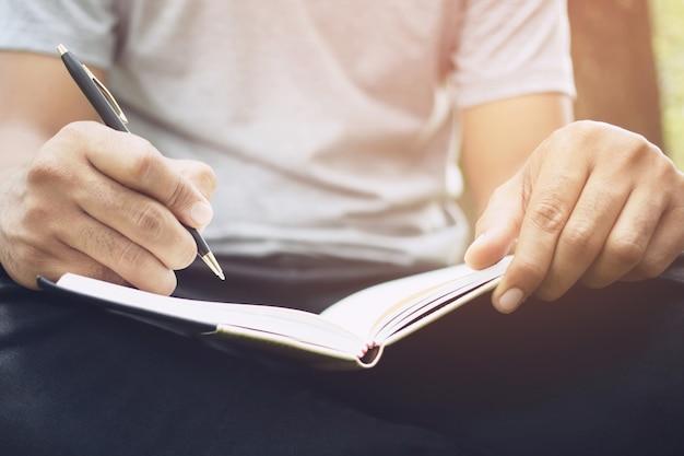 Feche a mão jovem está sentada em uma cadeira de mármore. usando a caneta para escrever um bloco de notas de palestra gravada no livro em um parque público.