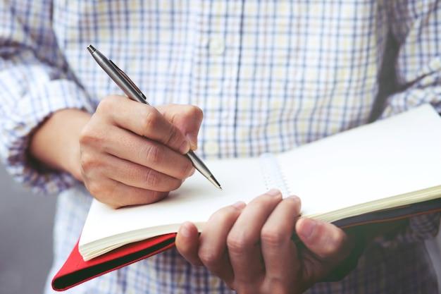Feche a mão jovem está sentada em uma cadeira de mármore. usando a caneta para escrever um bloco de notas de palestra gravada no livro no parque público. vista do topo