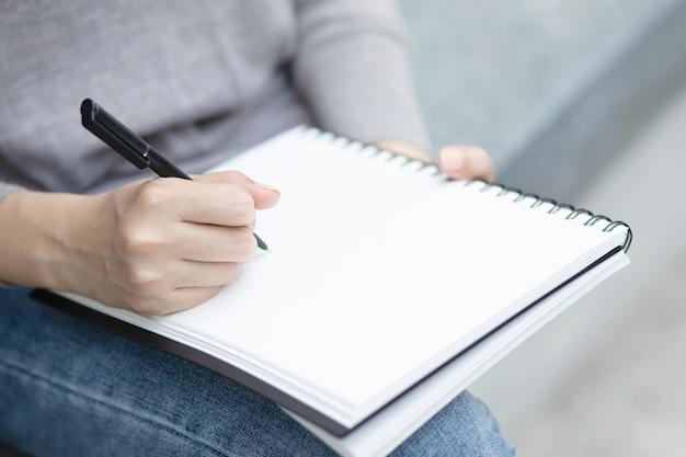 Feche a mão jovem está sentado em uma cadeira de mármore. usando a caneta para escrever um bloco de notas de palestra no livro em um parque público.