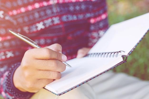 Feche a mão jovem está sentado usando a caneta para escrever o bloco de notas de aula de registro no livro sobre a madeira da mesa.