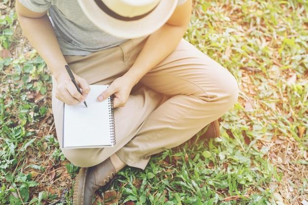 Feche a mão, jovem sentado, usando a caneta para escrever