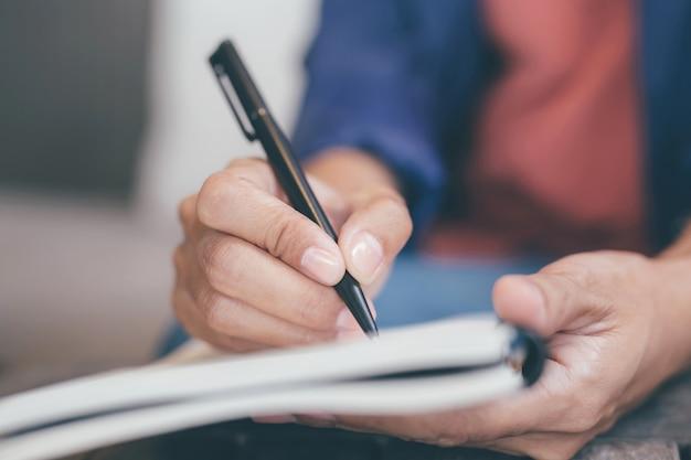 Feche a mão, jovem, usando uma caneta para escrever um bloco de notas de palestra no livro sentado na cadeira ao ar livre