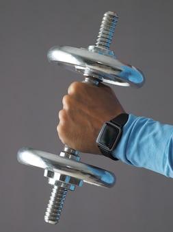 Feche a mão masculina usando smartwatch e segurando halteres