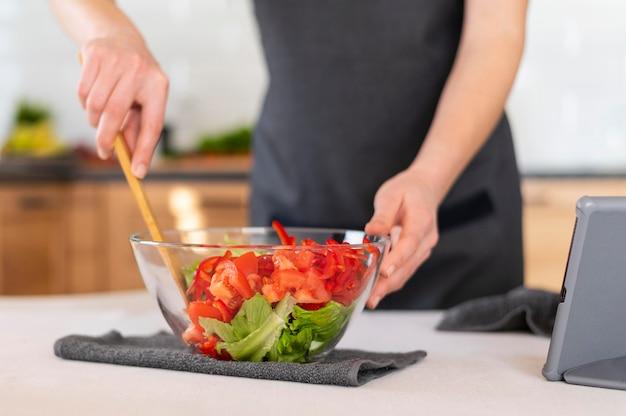 Feche a mão misturando salada