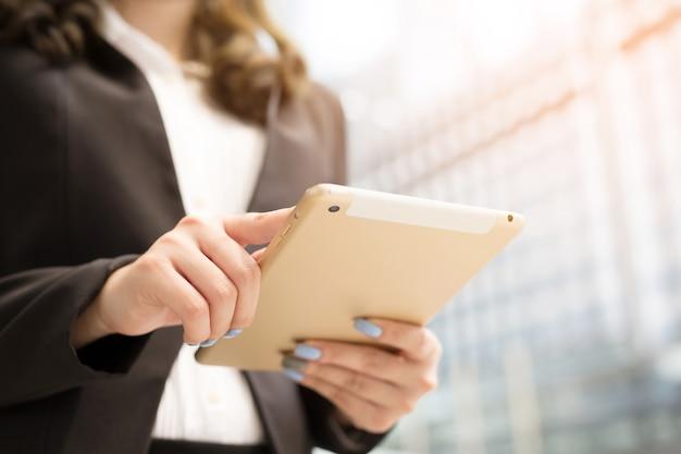 Feche a mão mulher de negócios trabalhando usando um tablet digital