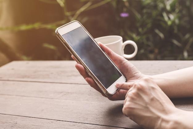 Feche a mão mulher segurando e usando o telefone na mesa de madeira com vintage tonificado.