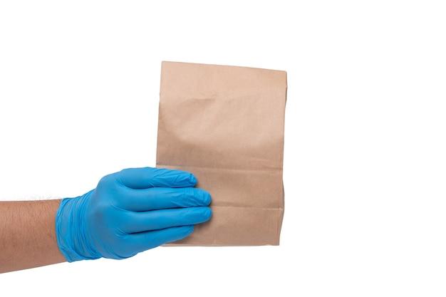 Feche a mão na luva médica e segurando o saco de papel de comida