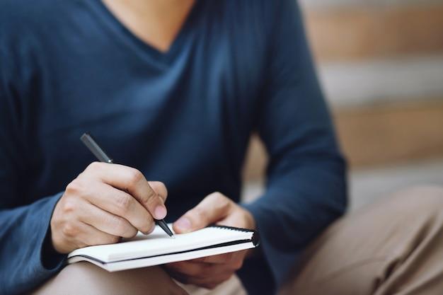 Feche a mão, o jovem está sentado usando uma caneta escrevendo um bloco de notas de aula para gravar no livro