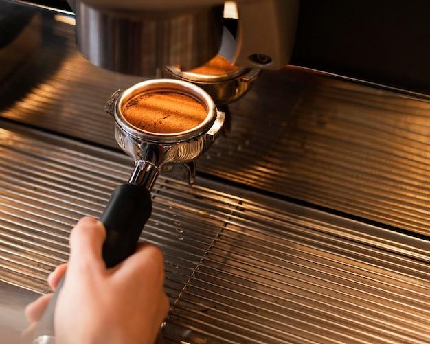 Feche a mão preparando o café com a máquina