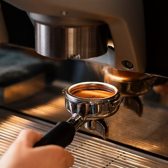 Feche a mão preparando o café