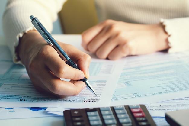 Feche a mão que arquiva o formulário de imposto dos eua. formulário de imposto nos negócios renda escritório mão preencher conceito