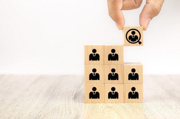 Feche a mão que escolhe ícones de pessoas em blocos de madeira do brinquedo do cubo, recursos humanos de conceitos.