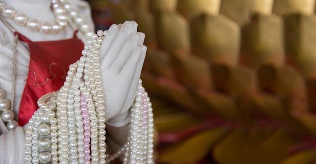 Feche a mão rezando da figura de mármore no templo chinês com uma pérola no tamanho do banner