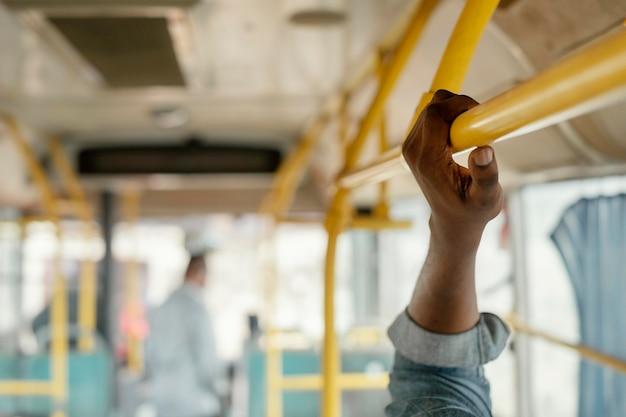 Feche a mão segurando a barra do ônibus