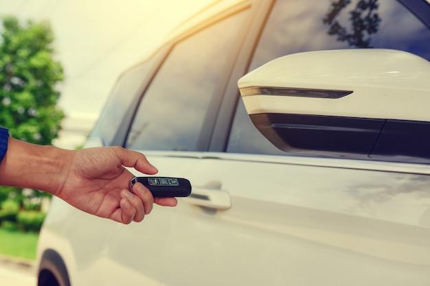 Feche a mão segurando a chave aberta da porta do carro