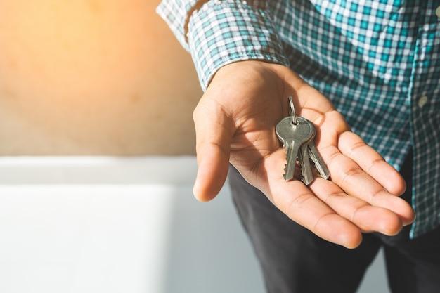 Feche a mão segurando a chave em casa.