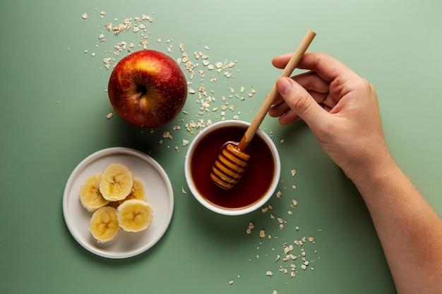 Feche a mão segurando a concha de mel