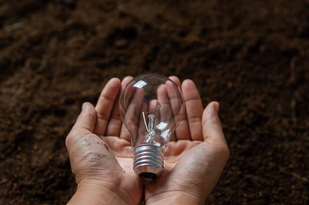 Feche a mão segurando a lâmpada com o conceito de solo, energia segura e meio ambiente
