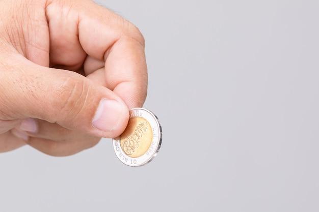 Feche a mão segurando a moeda da tailândia (10 baht).