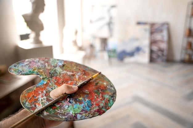 Feche a mão segurando a paleta de pintura