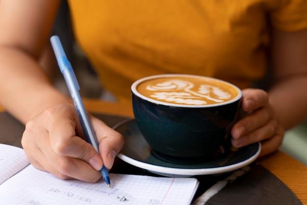 Feche a mão segurando a xícara de café