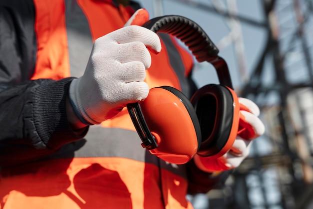 Feche a mão segurando fones de ouvido de proteção