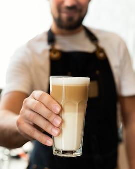Feche a mão segurando o café com leite