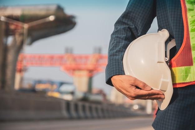 Feche a mão segurando o fundo de construção do local do capacete, proteção do capacete do engenheiro de arquitetura