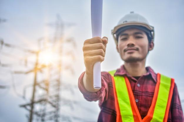 Feche a mão segurando o papel, engenheiro segurando o plano de papel para usar no trabalho