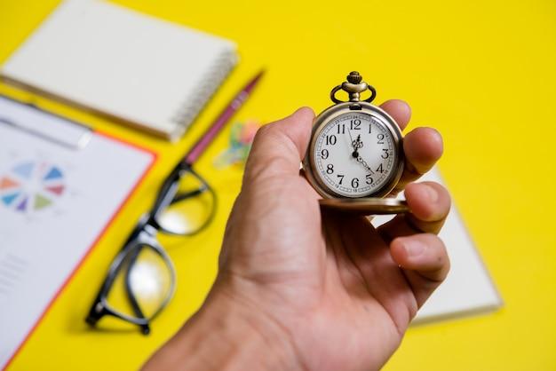 Feche a mão segurando o relógio