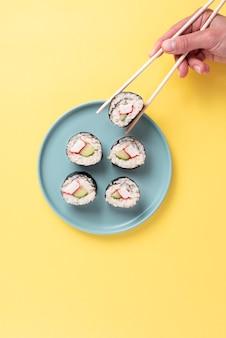 Feche a mão segurando o sushi com os pauzinhos