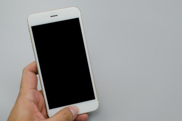 Feche a mão segurando o telefone preto sobre fundo cinza.