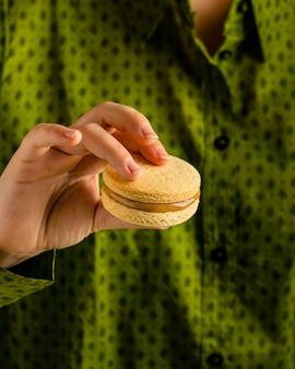 Feche a mão segurando um biscoito saboroso