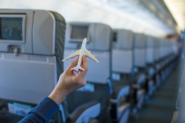 Feche a mão segurando um modelo de avião dentro de uma aeronave grande