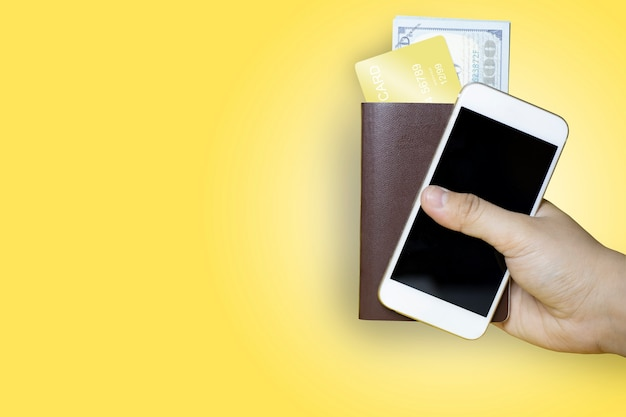 Feche a mão segurando um passaporte marrom e um telefone celular com uma nota de dólar e um cartão de crédito dourado dentro, fundo amarelo, passaporte usado para viagens internacionais, caminho de recorte.