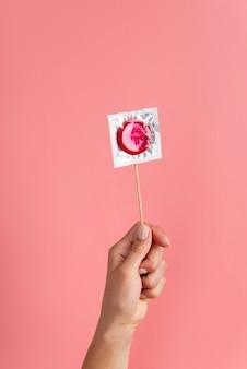 Feche a mão segurando um preservativo vermelho
